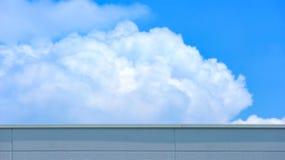 Betongvägg av hög byggnad med bakgrund för suddigt moln och för blå himmel arkivbild