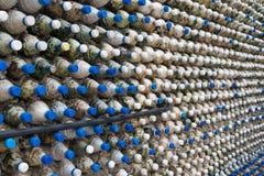Betongvägg som göras av återanvända plast- flaskor Arkivbild