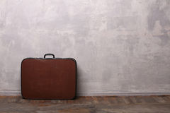 Betongväggar och trägolv med resväskan Arkivbilder