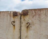 Betonmauer, die aus it& x27 heraus haftet; rostige Scharniere s für Transport Lizenzfreie Stockbilder