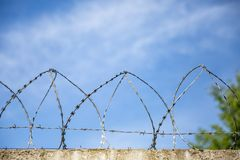 Betonmauer, gegen den Hintergrund des Stacheldrahts, das Konzept des Gefängnisses, Rettung, Flüchtling, einsam lizenzfreies stockbild