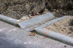 Betonowy odpływ woda przy asfaltową drogą Foremny miejsce fo fotografia stock