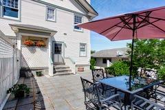 Betonowy podłogowy wygodny patio teren z stołu setem i patio parasolem Zdjęcie Royalty Free