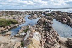 Betonowy stół i krzesła przy odosobnioną plażą z skałami obrazy royalty free
