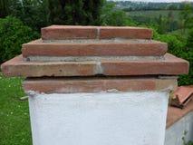 Betonpfosten am Ende einer Wand mit einer Kappe des roten Backsteins stockfotografie