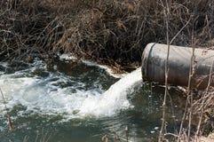 Betonrohr, das den verunreinigten Fluss transportiert Stockfotos