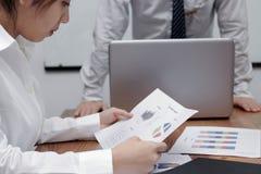 Betonte asiatische Geschäftsfrau, die Diagramme oder Schreibarbeit während der Sitzung im Konferenzsaal analysiert stockfotos