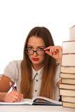 Betonte asiatische kaukasische Studentin, die in den Tonnen Büchern lernt Stockfotos