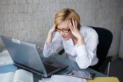 Betonte blonde Geschäftsfrau mit Laptop Lizenzfreie Stockfotos