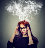 Betonte Frau, die den zu harten Dampf oben herauskommt vom Kopf denkt lizenzfreie stockfotografie