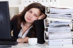 Betonte Frau, die im Büro arbeitet Lizenzfreie Stockfotos