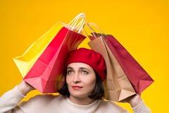 Betonte Frau müde vom Einkaufen Junge Frau im Barett unter Einkaufstaschen Saisonverkäufe, Einkaufskonzept Frau nach dem Einkauf lizenzfreie stockfotos