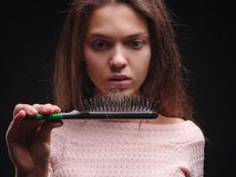 Betonte Frau mit Haarproblemen auf einem schwarzen Hintergrund Vitamine für zerbrechliches Haar Haar-Behandlungs-Konzept Kopieren Lizenzfreie Stockfotos