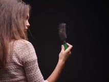 Betonte Frau mit Haarproblemen auf einem schwarzen Hintergrund Vitamine für zerbrechliches Haar Haar-Behandlungs-Konzept Kopieren Lizenzfreie Stockfotografie