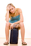 Betonte Frau mit Koffer Stockfoto