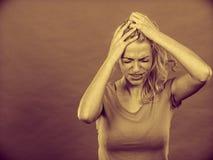 Betonte, frustrierte, deprimierte junge Frau in den Schmerz Stockfoto
