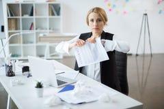 Betonte Geschäftsfrau am Arbeitsplatz lizenzfreie stockfotografie