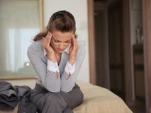 Betonte Geschäftsfrau, die auf Bett im Hotel sitzt lizenzfreie stockbilder
