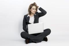 Betonte Geschäftsfrau, die auf dem Fußboden sitzt. Lizenzfreie Stockfotografie
