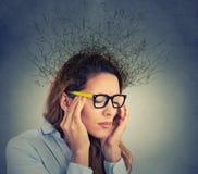 Betonte Geschäftsfrau, die das Kopfschmerzengehirn schmilzt in Linien Fragezeichen hat Stockfoto