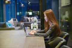 Betonte Geschäftsfrau, die einen Laptop im Wohnzimmer nachts verwendet lizenzfreies stockfoto