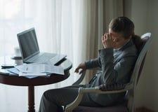 Betonte Geschäftsfrau, die im Hotelzimmer arbeitet Stockbilder