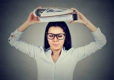 Betonte Geschäftsfrau, die mit Ordnern auf ihrem Kopf steht stockbilder