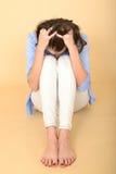 Betonte junge Frau, die auf dem Boden mit Kopf in den Händen sitzt Lizenzfreie Stockfotos