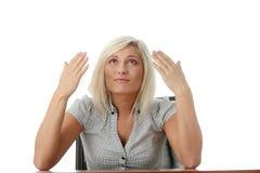 Betonte junge Frau, die hinter einem Schreibtisch sitzt Stockfotografie