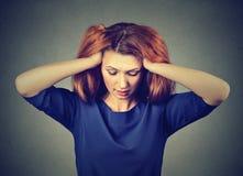 Betonte junge Frau mit den Kopfschmerzen, die unten schauen lizenzfreie stockfotografie