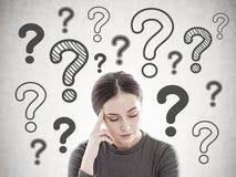 Betonte junge Frau mit Kopfschmerzen, Fragezeichen lizenzfreie stockfotografie
