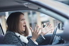 Betonte junge Geschäftsfrau, die ihr Auto fährt stockbild