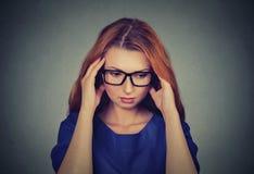 Betonte junge RothaarigeGeschäftsfrau, die Kopfschmerzen hat Stockfotografie