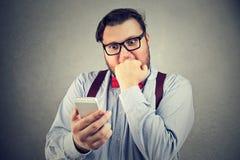 Betonte Mannlesenachrichten auf Smartphone stockbilder