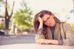 Betonte traurige junge Frau, die draußen sitzt lizenzfreie stockbilder