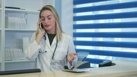 Betonte weibliche medizinische schreiende Arbeitskraft beim Sprechen am Telefon an der Krankenhausaufnahme stock video