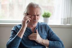 Betonter älterer Mann, der Herzinfarkt bei der Unterhaltung am Telefon hat lizenzfreie stockfotos