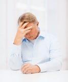 Betonter alter Mann, der zu Hause Kopf hält Lizenzfreie Stockbilder