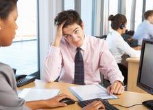 Betonter Angestellter, der im beschäftigten Büro arbeitet Lizenzfreies Stockfoto