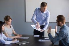 Betonter Angestellter sind mit dem Chef anderer Meinung, der für Fehler im Repo tadelt lizenzfreie stockbilder