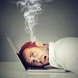 Betonter Angestelltmann mit überhitztem Gehirn unter Verwendung des Laptops stockfotos