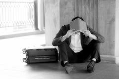 Betonter asiatischer Geschäftsmann bankrott mit dem Sitzen an draußen Stockfotografie