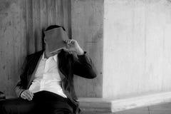 Betonter asiatischer Geschäftsmann bankrott mit dem Sitzen an im Freien Stockbilder