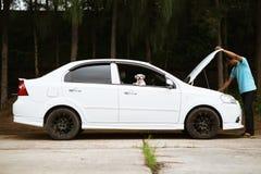 Betonter asiatischer Mann, der die Maschine des defekten Autos mit seinem betrachtet lizenzfreie stockfotografie