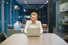 Betonter blonder Geschäftsmann, der einen Laptop im Wohnzimmer an Ni verwendet Stockfoto