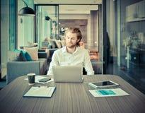 Betonter blonder Geschäftsmann, der einen Laptop im Wohnzimmer an Ni verwendet Lizenzfreie Stockbilder