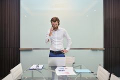 Betonter blonder Geschäftsmann, der am Telefon mit leerem gla spricht Lizenzfreie Stockfotos
