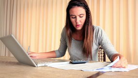 Betonter Brunette, der ihre Finanzen mit Laptop ausarbeitet stock video