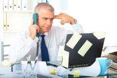 Betonter Geschäftsmann, der am Schreibtisch sitzt stockfotografie