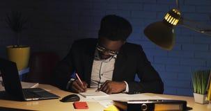 Betonter Geschäftsmann versehentlich verwirrt in den Dokumenten, die am Schreibtisch im Nachtbüro arbeiten Workaholic, das Friste stock video footage